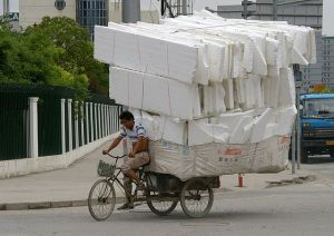 A man is riding a tricycle with heavy load on the streets of Shanghai - by Jakub Hałun